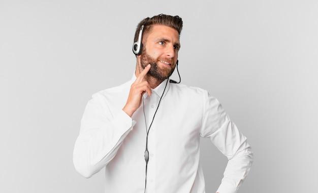 Jonge knappe man die vrolijk lacht en dagdroomt of twijfelt. telemarketing concept