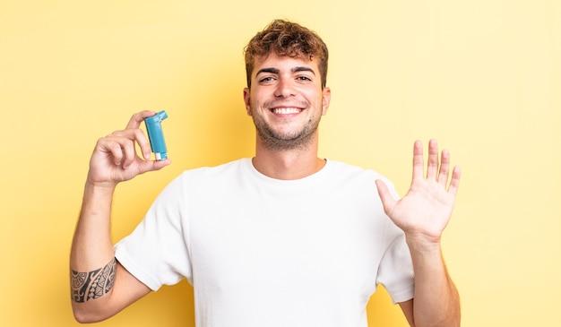 Jonge knappe man die vrolijk lacht, met de hand zwaait, je verwelkomt en begroet. astma concept