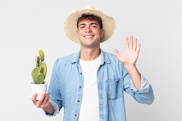 Jonge knappe man die vrolijk lacht, met de hand zwaait, je verwelkomt en begroet. boer met een decoratieve cactus