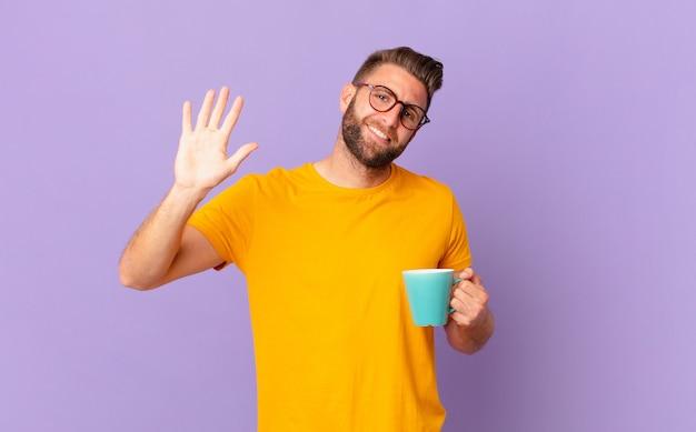 Jonge knappe man die vrolijk lacht, met de hand zwaait, je verwelkomt en begroet. en een koffiemok vasthouden