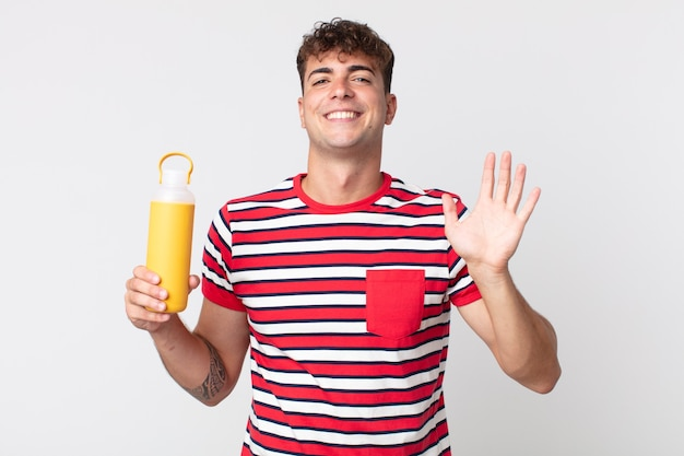 Jonge knappe man die vrolijk lacht, met de hand zwaait, je verwelkomt en begroet en een koffiethermos vasthoudt