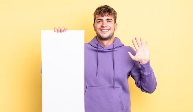 Jonge knappe man die vrolijk lacht, met de hand zwaait, je verwelkomt en begroet. kopieer ruimteconcept