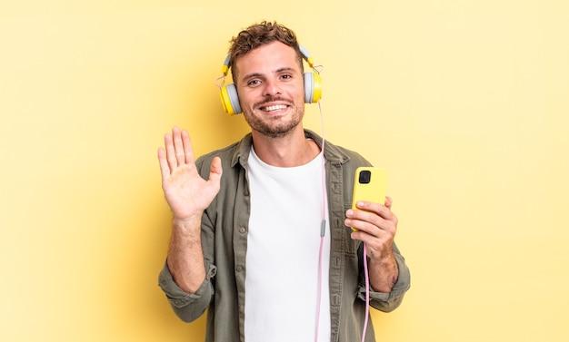 Jonge knappe man die vrolijk lacht, met de hand zwaait, je verwelkomt en begroet met koptelefoon en smartphone concept