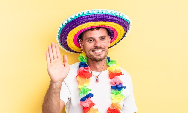 Jonge knappe man die vrolijk lacht, met de hand zwaait, je verwelkomt en begroet. mexicaans feestconcept