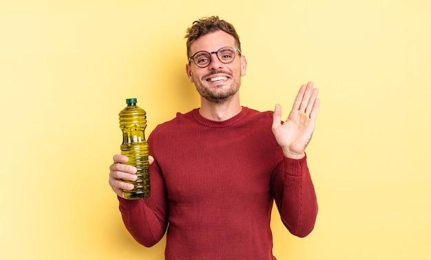 Jonge knappe man die vrolijk lacht, met de hand zwaait, je verwelkomt en begroet. olijfolie concept