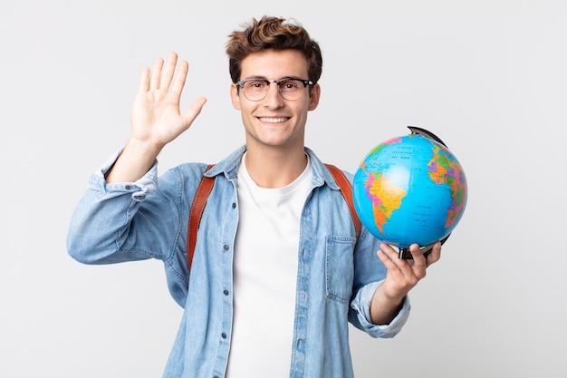 Jonge knappe man die vrolijk lacht, met de hand zwaait, je verwelkomt en begroet. student met een wereldbolkaart