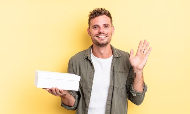 Jonge knappe man die vrolijk lacht, met de hand zwaait, je verwelkomt en begroet. witte doos concept