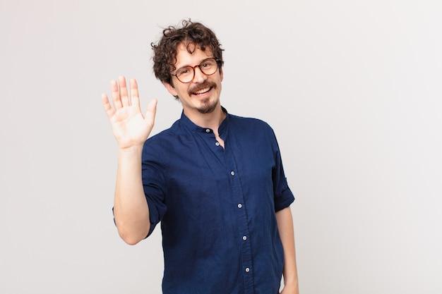 Jonge knappe man die vrolijk lacht, met de hand zwaait, je verwelkomt en begroet