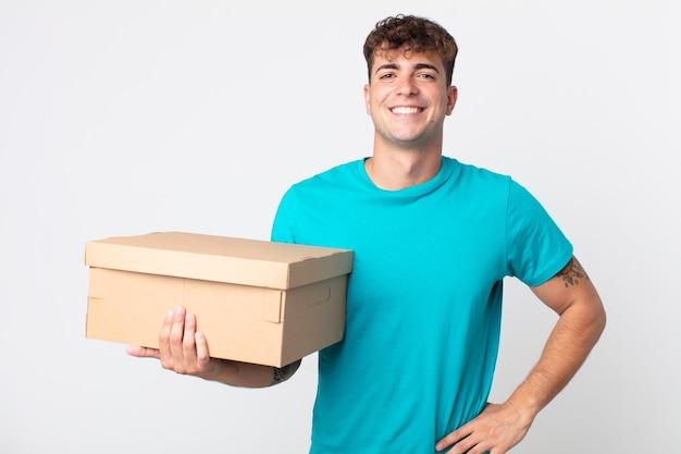 Jonge knappe man die vrolijk lacht met een hand op de heup en zelfverzekerd en een kartonnen doos vasthoudt