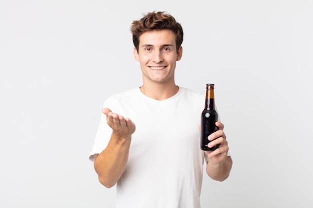 Jonge knappe man die vrolijk lacht met vriendelijk en een concept aanbiedt en toont en een bierfles vasthoudt