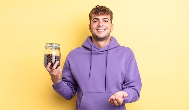 Jonge knappe man die vrolijk lacht met vriendelijk en een concept aanbiedt en toont. koffiebonen concept