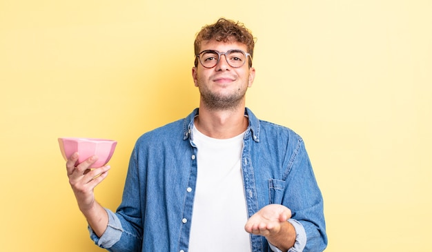 Jonge knappe man die vrolijk lacht met vriendelijk en een concept aanbiedt en toont. lege kom concept