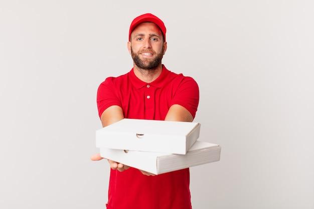 Jonge knappe man die vrolijk lacht met vriendelijk en een concept aanbiedt en toont. pizza bezorgconcept