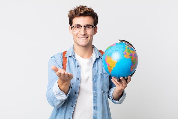 Jonge knappe man die vrolijk lacht met vriendelijk en een concept aanbiedt en toont. student met een wereldbolkaart