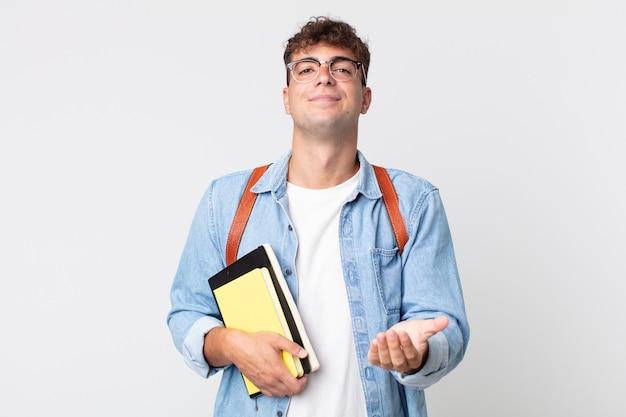 Jonge knappe man die vrolijk lacht met vriendelijk en een concept aanbiedt en toont. universitair studentenconcept