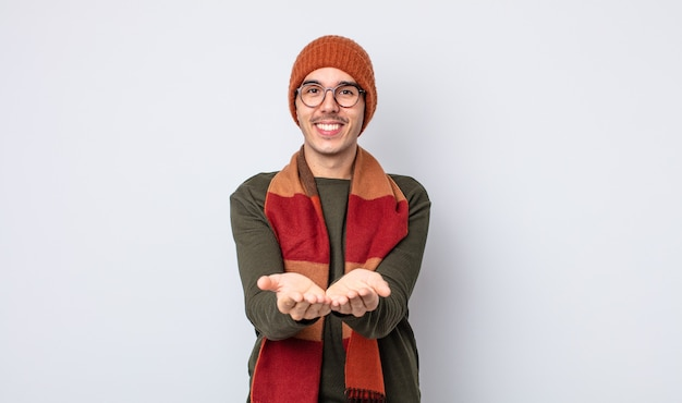 Jonge knappe man die vrolijk lacht met vriendelijk en een concept aanbiedt en toont. winterkleren concept