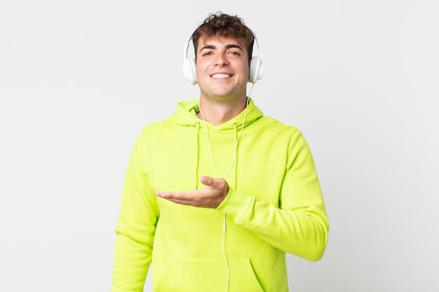 Jonge knappe man die vrolijk lacht, zich gelukkig voelt en een concept en een koptelefoon laat zien