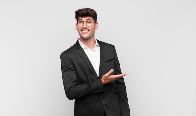 Jonge knappe man die vrolijk lacht, zich gelukkig voelt en een concept in kopieerruimte toont met de palm van de hand