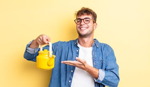 Jonge knappe man die vrolijk lacht, zich gelukkig voelt en een concept.teapot-concept toont