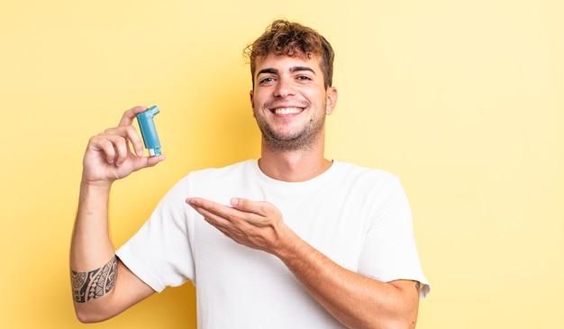 Jonge knappe man die vrolijk lacht, zich gelukkig voelt en een concept toont. astma concept