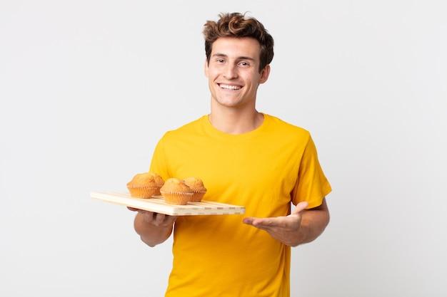 Jonge knappe man die vrolijk lacht, zich gelukkig voelt en een concept toont met een dienblad met muffins