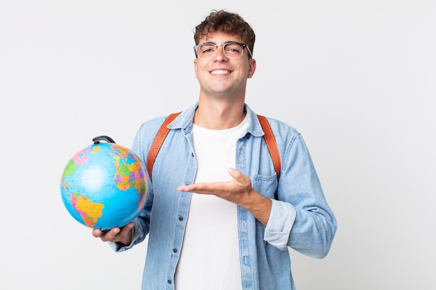 Jonge knappe man die vrolijk lacht, zich gelukkig voelt en een concept toont. student met een wereldbolkaart
