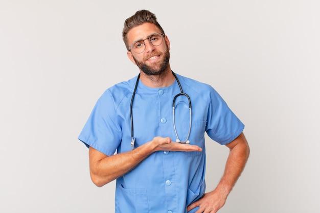 Jonge knappe man die vrolijk lacht, zich gelukkig voelt en een concept toont. verpleegster concept