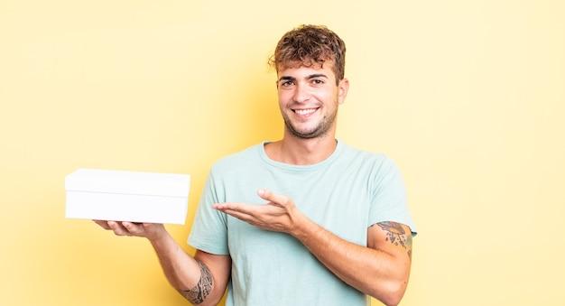 Jonge knappe man die vrolijk lacht, zich gelukkig voelt en een concept toont. witte doos concept