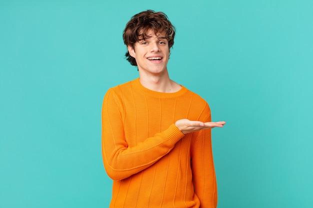 Jonge knappe man die vrolijk lacht, zich gelukkig voelt en een concept toont