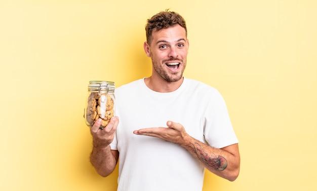 Jonge knappe man die vrolijk lacht, zich gelukkig voelt en een concept voor een fles met koekjes toont
