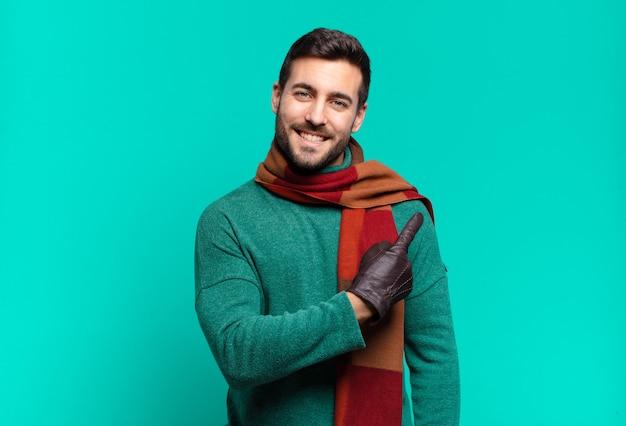 Jonge knappe man die vrolijk lacht, zich gelukkig voelt en naar de zijkant en naar boven wijst, object in kopie ruimte toont. koude en winter concept