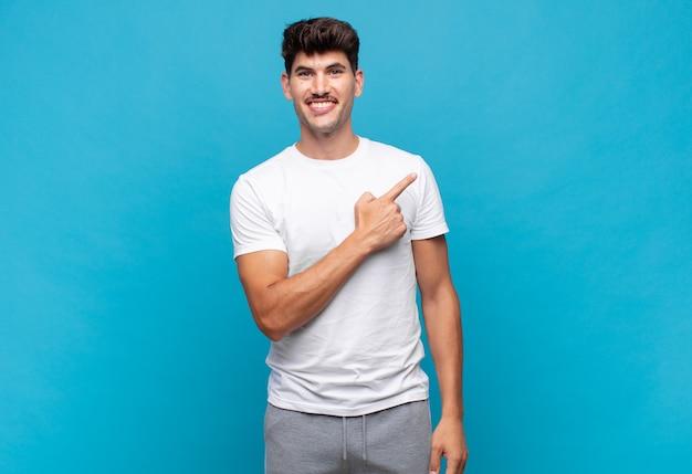 Jonge knappe man die vrolijk lacht, zich gelukkig voelt en naar de zijkant en naar boven wijst, object in kopie ruimte toont