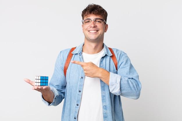 Jonge knappe man die vrolijk lacht, zich gelukkig voelt en naar de zijkant wijst. intelligentie spelconcept