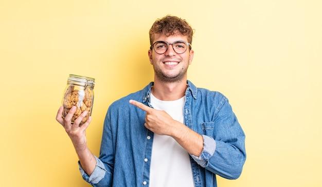 Jonge knappe man die vrolijk lacht, zich gelukkig voelt en naar de zijkant wijst. koekjes fles concept