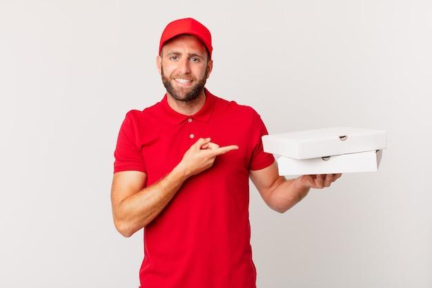 Jonge knappe man die vrolijk lacht, zich gelukkig voelt en naar de zijkant wijst. pizza bezorgconcept
