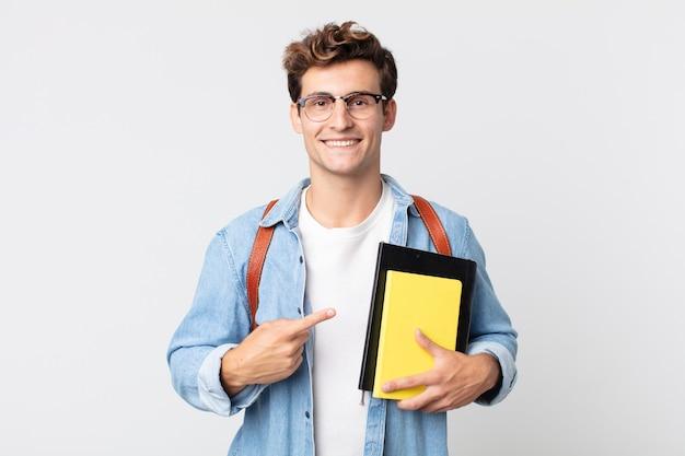 Jonge knappe man die vrolijk lacht, zich gelukkig voelt en naar de zijkant wijst. universitair studentenconcept