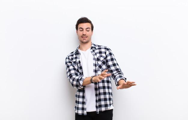 Jonge knappe man die walgt en misselijk voelt, zich terugtrekt voor iets smerigs, stinkende of stinkende, zegt bah op een witte muur