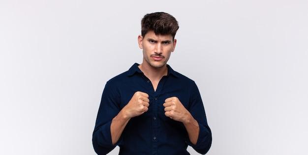 Jonge knappe man die zelfverzekerd, boos, sterk en agressief kijkt, met vuisten klaar om te vechten in bokspositie