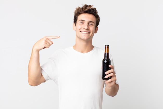 Jonge knappe man die zelfverzekerd glimlacht, wijst naar zijn eigen brede glimlach en een bierfles vasthoudt