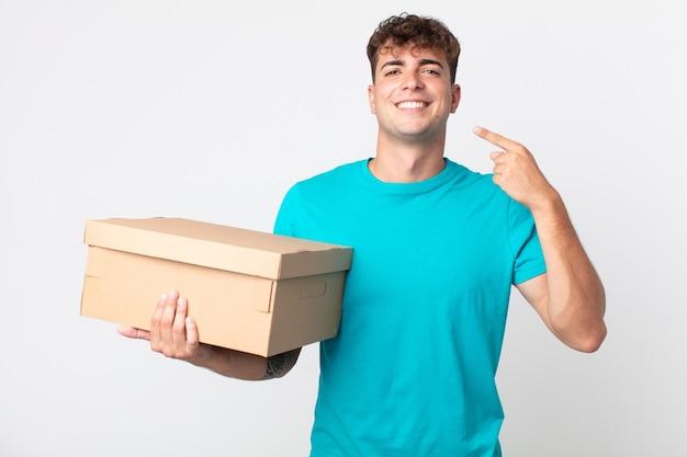 Jonge knappe man die zelfverzekerd glimlacht, wijst naar zijn eigen brede glimlach en een kartonnen doos vasthoudt