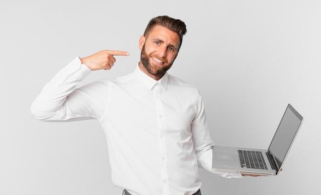 Jonge knappe man die zelfverzekerd glimlacht, wijst naar zijn eigen brede glimlach en een laptop vasthoudt