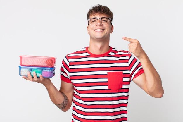 Jonge knappe man die zelfverzekerd glimlacht, wijst naar zijn eigen brede glimlach en een lunchbox vasthoudt Premium Foto