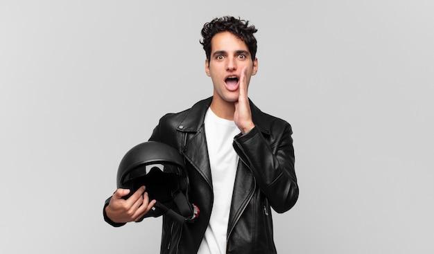 Jonge knappe man die zich blij, opgewonden en positief voelt, een grote schreeuw geeft met de handen naast de mond, roept. motorrijder concept