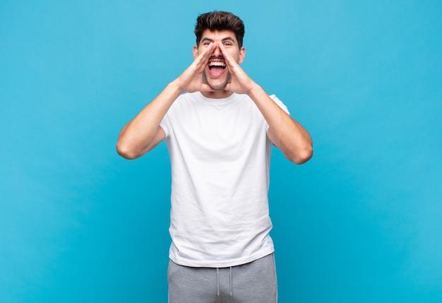 Jonge knappe man die zich blij, opgewonden en positief voelt, een grote schreeuw geeft met de handen naast de mond, roept