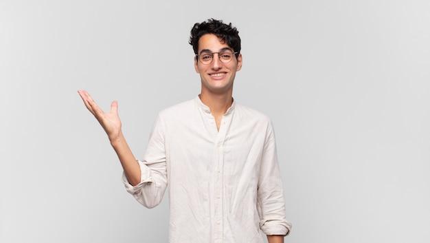 Jonge knappe man die zich blij, verrast en opgewekt voelt, lacht met een positieve houding, een oplossing of idee realiseert