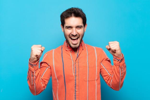Jonge knappe man die zich blij, verrast en trots voelt, schreeuwt en succes viert met een grote glimlach