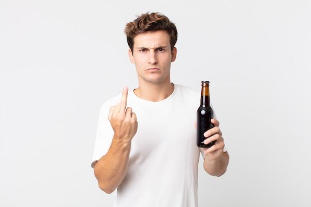 Jonge knappe man die zich boos, geïrriteerd, opstandig en agressief voelt en een bierflesje vasthoudt