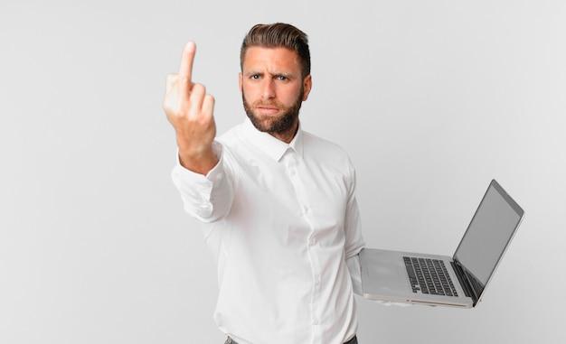 Jonge knappe man die zich boos, geïrriteerd, opstandig en agressief voelt en een laptop vasthoudt