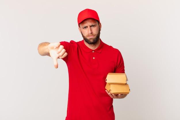 Jonge knappe man die zich boos voelt, duim omlaag laat zien hamburger die concept levert