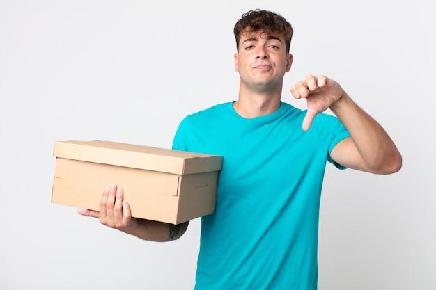 Jonge knappe man die zich boos voelt, duimen naar beneden laat zien en een kartonnen doos vasthoudt